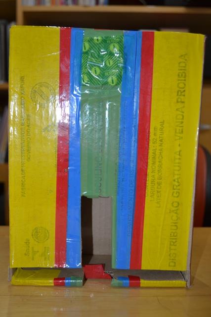 Primeiro dispensador de preservativo, feito a partir da própria embalagem de papelão. Depois vieram os de acrílico