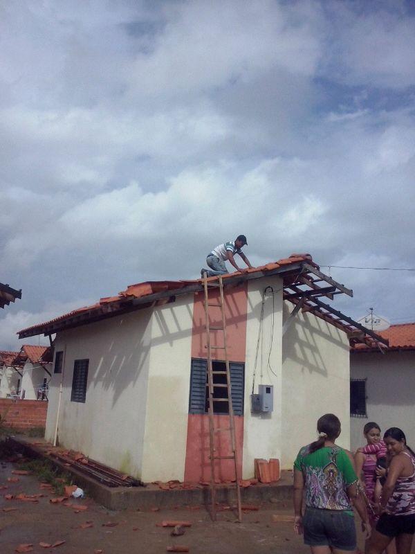 Moradores fazendo reparos nos telhados. Não há registros de feridos