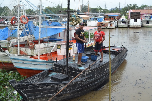 Valdo Dias e Arildo Souza limpando o barco Deus te Guie