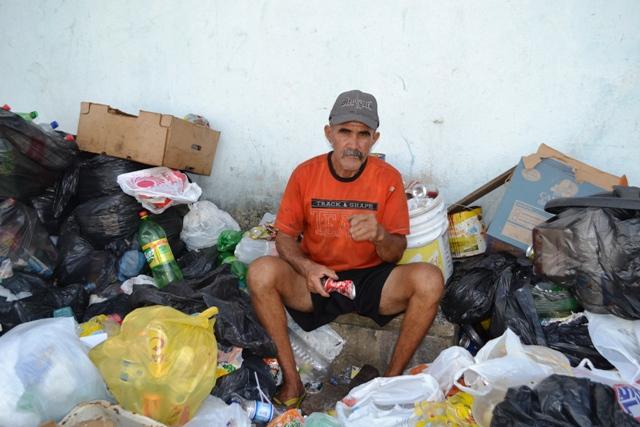 Francisco dos Santos cercado de lixo. Vizinhos dizem que ele dorme na praça do bairro