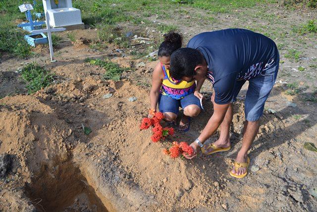 Pais depositam flores no sepultura de Maria Helena