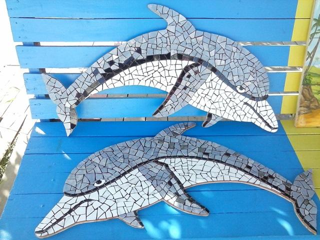 Dois golfinhos formados por um quebra-cabeças com restos de lajotas