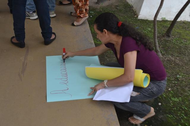 Professora prepara cartaz para a manifestação