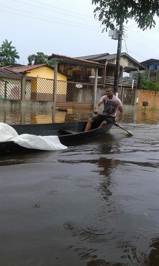 As pessoas estão utilizando pequenos barcos para se locomoverem nas ruas