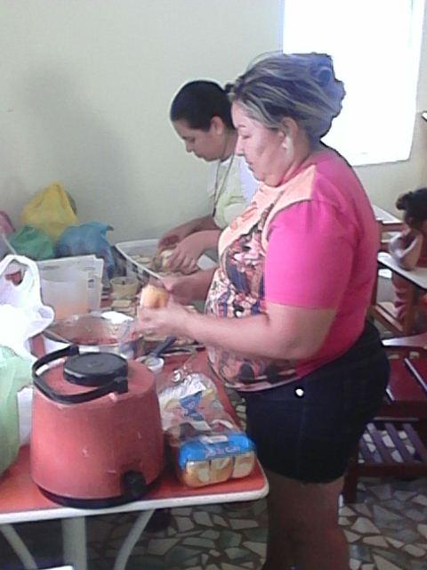 Voluntários preparam o alimento para as crianças