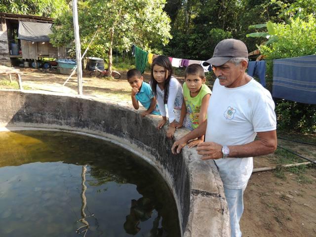 Seu Bené, com os filhos, mostra um dos tanques onde cria tartarugas e tracajás