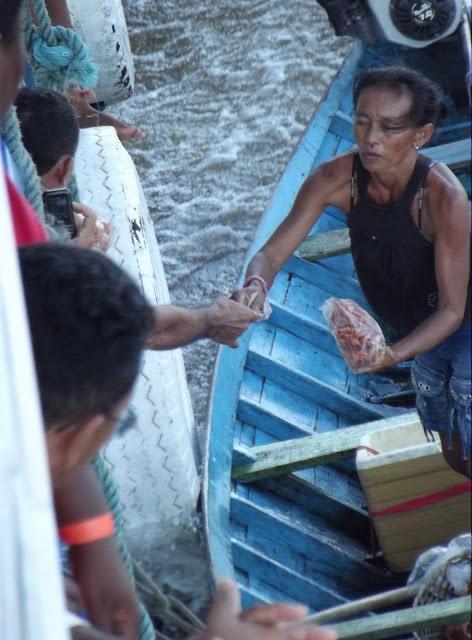 """Depois de """"laçar"""" o navio,  ribeirinha vende camarão e açaí aos passageiros"""