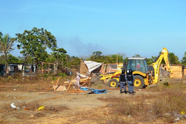 Policiais observam a demolição de barracos