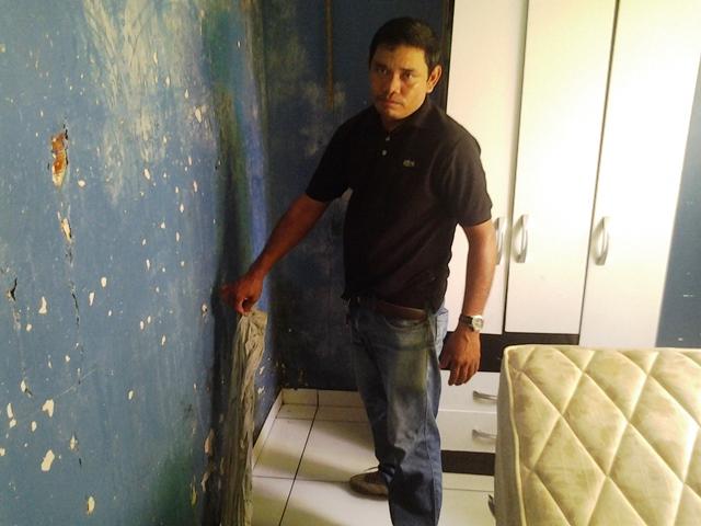Davi mostra as infiltrações que percorrem todas as paredes. Fotos: André Silva