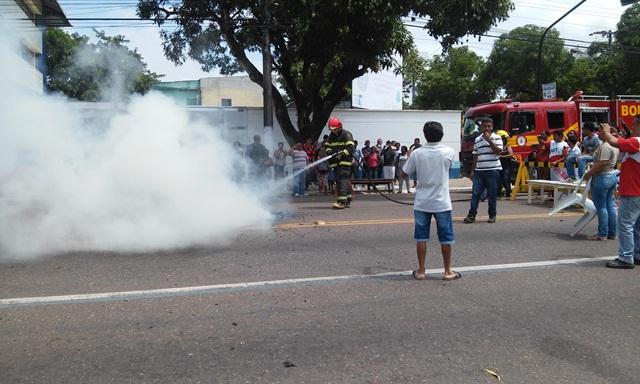 Bombeiros apagam o fogo em pneus no meio da Avenida FAB. Fotos: Cássia Lima