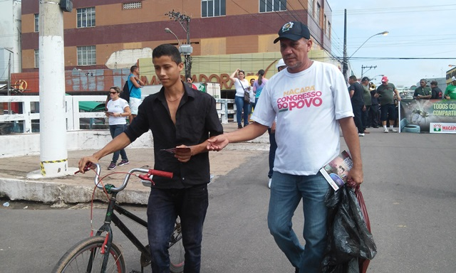 Agente de endemias entrega panfleto a um jovem
