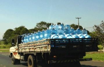 Caminhão transportando garrafões no sol