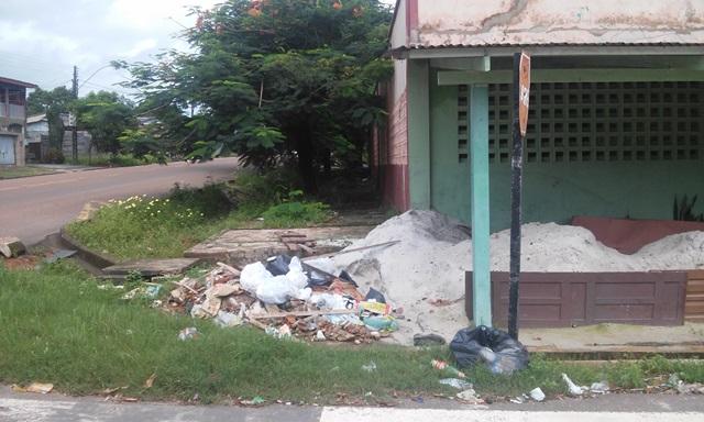 Lixo e mato no entorno do prédio