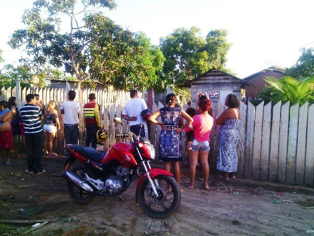 Moradores observam corpo do menor na casa onde ele teria ido pedir ajuda