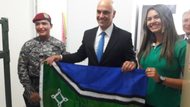 Ministro Alexandre de Moraes segura a Bandeira do Amapá entre a cabo Adriele e a Sargento Solange (verde), da Corregedoria da PM