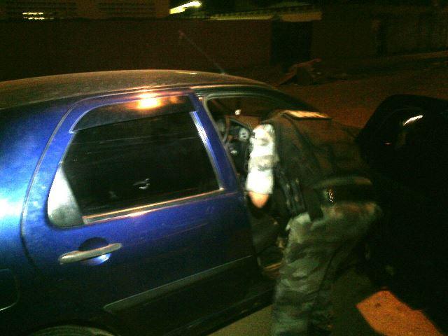 Policial revista carro onde estavam os criminosos. Fotos: Olho de Boto
