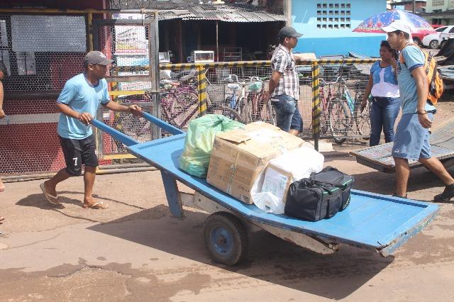 Carregadores atravessam mercadorias e bagagens das embarcações para a saída do porto
