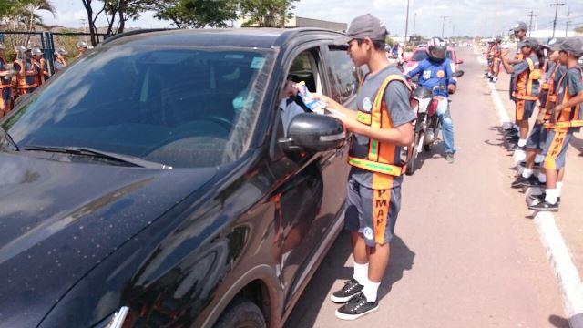 Garoto do projeto entrega panfleto a motorista: compartilhando informações