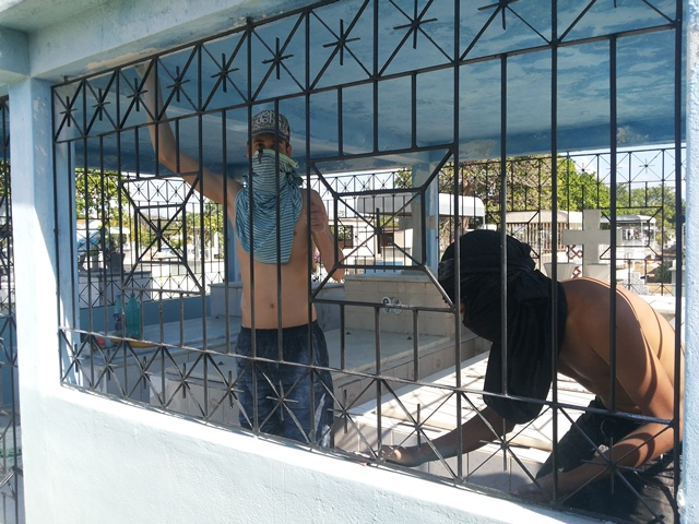 Felipe e Willian, trabalhando na limpeza de sepulturas