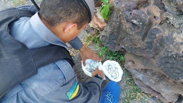 Policial checa dois sacos com maconha retirados das pedras do monumento. Fotos: Olho de Boto