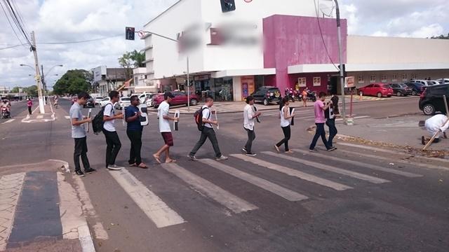 Jovens se posicionamento em cruzamento quando o semáforo fica vermelho