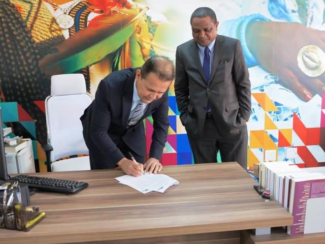 Observado pelo presidente da Fundação Palmares, Erivaldo Oliveira, deputado Marcos Reátegui assina liberação de R$ 1 milhão para a Virada Afro. Foto: Divulgação