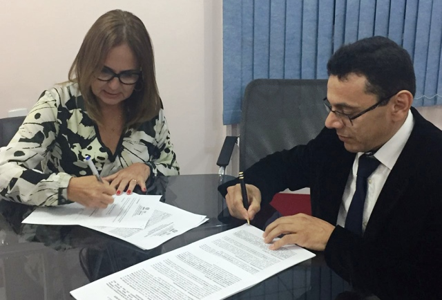 Secretária de Educação, Goreth Souza, e representante da empresa assinam contrato: áreas de entorno das escolas também serão cobertas. Foto: Ruan Alves/Secom