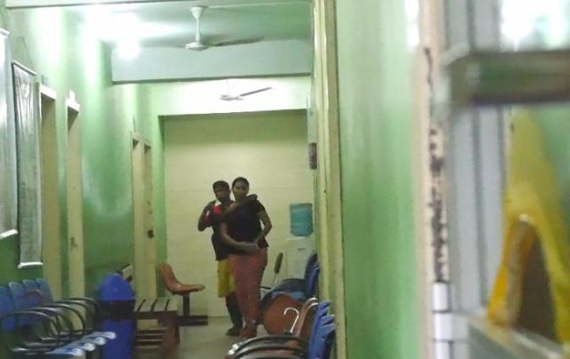 Bandido caminha por corredor com arma apontada para a refém...