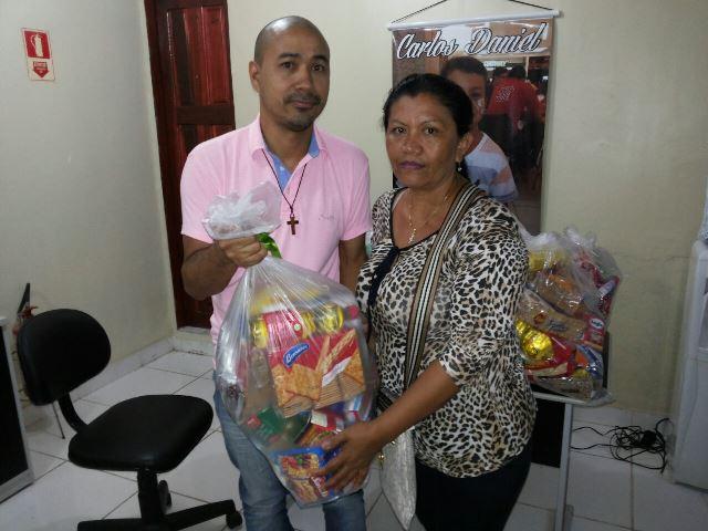 Raimunda recebe cesta de alimento. Fotos: Ong Carlos Daniel