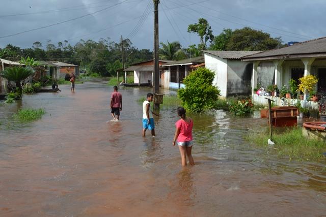 Crianças e adultos caminham por uma das muitas ruas submersas