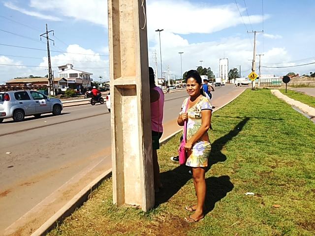 À sombra de um poste, usuários esperam ônibus