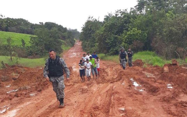 Agentes penitenciários e presos caminham na lama para vencer atoleiros