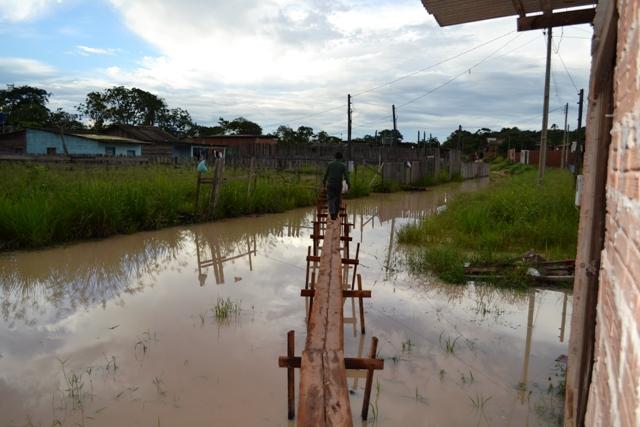 Moradores improvisam ponte para atravessar rua alagada