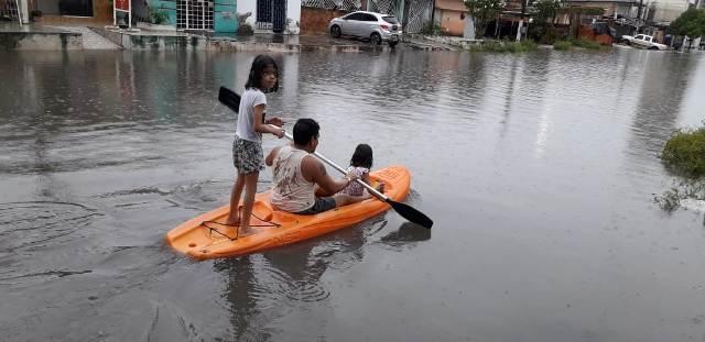 Moradores de avenida alagada em Macapá usam caiaque