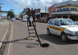 Moradores usam até escada para alertar sobre buraco em rua